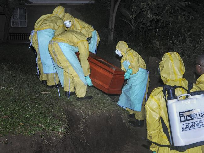 Workers wearing protective clothing bury Agnes Mbambu. Picture: Ronald Kabuubi