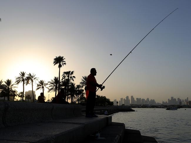 A man fishes off the cornice in the Qatari capital Doha on July 2, 2017.