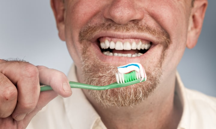 A smiling man with a goatee beard holds a toothbrush loaded with toothpaste up to his mouth.