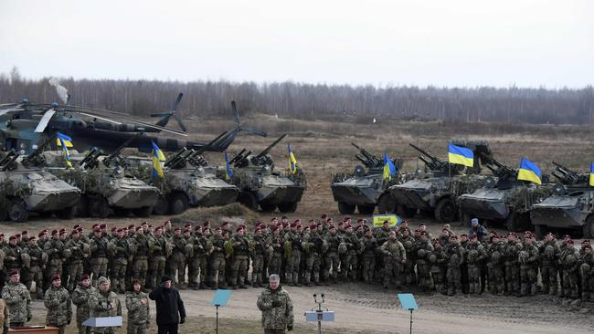 Ukrainian President Petro Poroshenko stands with Ukrainian servicemen of the airborne troops as they sing the Ukrainian national anthem. Picture: AFP