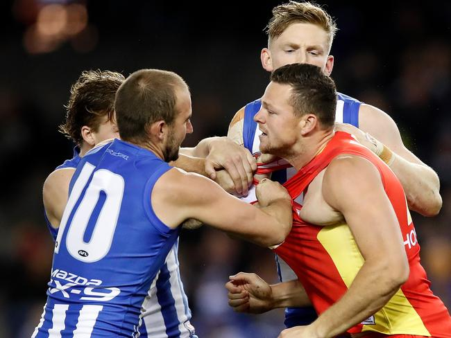 Ben Cunnington (left) and Jack Ziebell remonstrate with Steven May of the Suns after a hit from May on Shaun Higgins . (Photo by Adam Trafford/AFL Media/Getty Images)