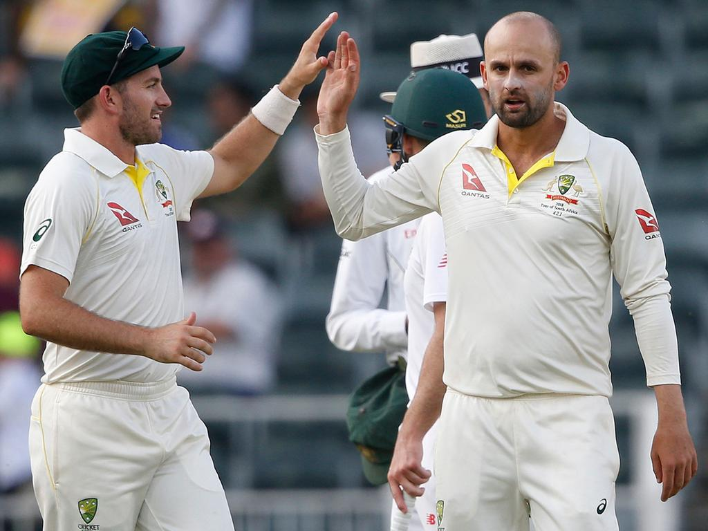 Australian bowler Nathan Lyon (R) celebrates the dismissal of South African batsman Hashim Amla (not in picture) on the third day of the fourth Test cricket match between South Africa and Australia at Wanderers cricket ground on April 1, 2018 in Johannesburg. / AFP PHOTO / GIANLUIGI GUERCIA