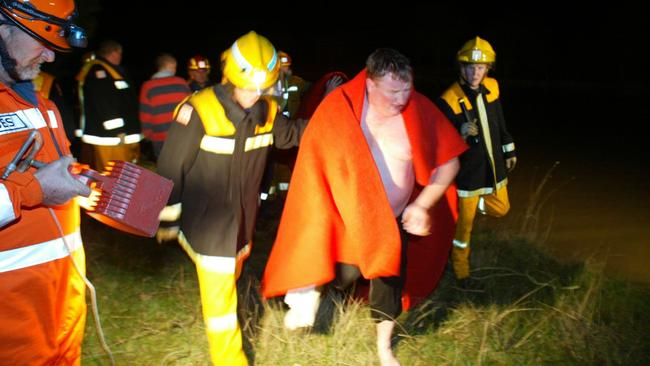 A CFA diver is helped from the dam after searching for the three boys near Winchelsea.