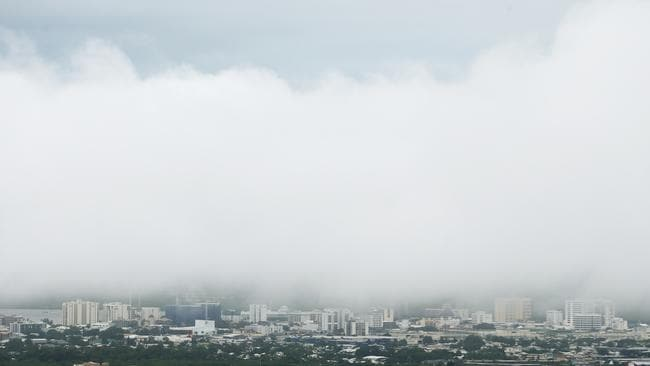 Cairns City remains covered in low cloud after heavy rain brought flooding and storm damage to the region. Picture: Brendan Radke