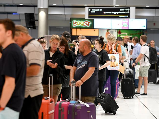 Queues of passengers after their flights were cancelled at Brisbane airport on Friday. Picture: John Gass.