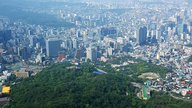 Go to the top of Namsan Tower for views of the city. It stretches out of sight in every direction — but there are huge pockets of green wherever you look.