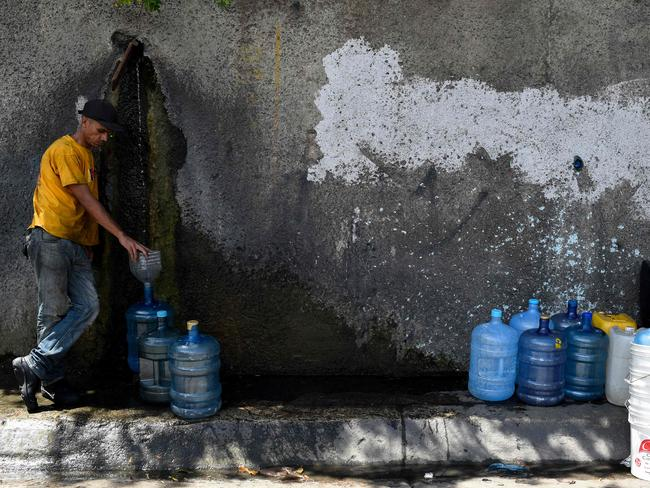A man fills a jerry can with water from the Wuaraira Repano mountain. Water rationing is a regular occurrence across this crisis-hit country which has huge water resources but a national infrastructure in very bad condition. Picture: AFP