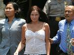 2004 - Schapelle Corby walks with officers after investigation at police headquarters in Denpasar on Indonesian resort island of Bali. Picture: Lukman S Bintoro