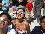 Alex Gamarra and Jessica Gamarra (L-R) view the solar eclipse at The Phillip and Patricia Frost Museum of Science on August 21, 2017 in Miami, Florida. Picture: Joe Raedle/Getty Images/AFP