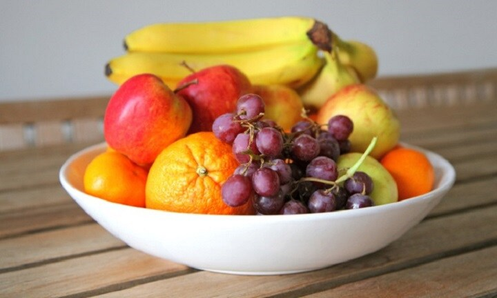a bowl of fresh fruit set on a wooden table