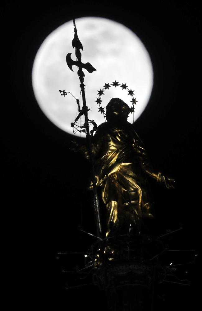 "The full moon rises behind the statue of the ""Madonnina"" Virgin Mary atop Milan's gothic-era Duomo Cathedral, in Milan, Italy, Tuesday, February 19, 2019. It is the year's second supermoon, when a full moon appears a little bigger and brighter thanks to its slightly closer position to Earth. Picture: Luca Bruno"