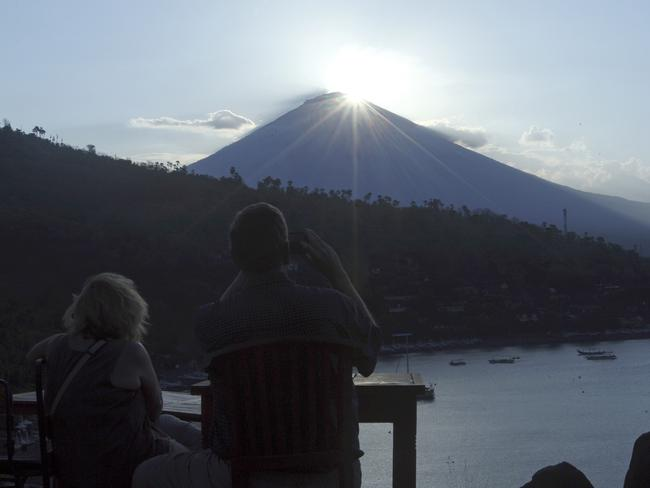 Tourists watch the sunset over Mount Agung in Karangasem on Thursday as Bali braces for the volcano to erupt. Picture: AP/Firdia Lisnawati