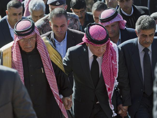 Jordanian King Abdullah II, center, escorted by Safi al-Kaseasbeh, left, father of slain Jordanian pilot, Lt. Muath al-Kaseasbeh, and his uncle Fahed al-Kaseasbeh, arrives to offer his condolences at the memorial tent. Picture: Nasser Nasser