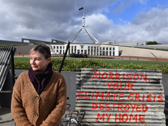 Melinda Plesman stands with the remains of her burnt out house, outside Parliament House in Canberra. Picture: Mick Tsikas/AAP
