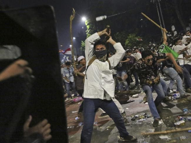 Protesters use sticks to attack riot police during a clash outside the presidential palace in Jakarta, Indonesia. Picture: Tatan Syuflana.