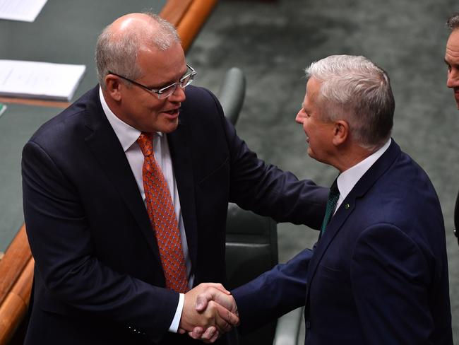 Prime Minister Scott Morrison is congratulated by Deputy Prime Minister Michael McCormack in the House of Representatives after the passing of the Government's income tax package plan. Picture: Sam Mooy/AAP