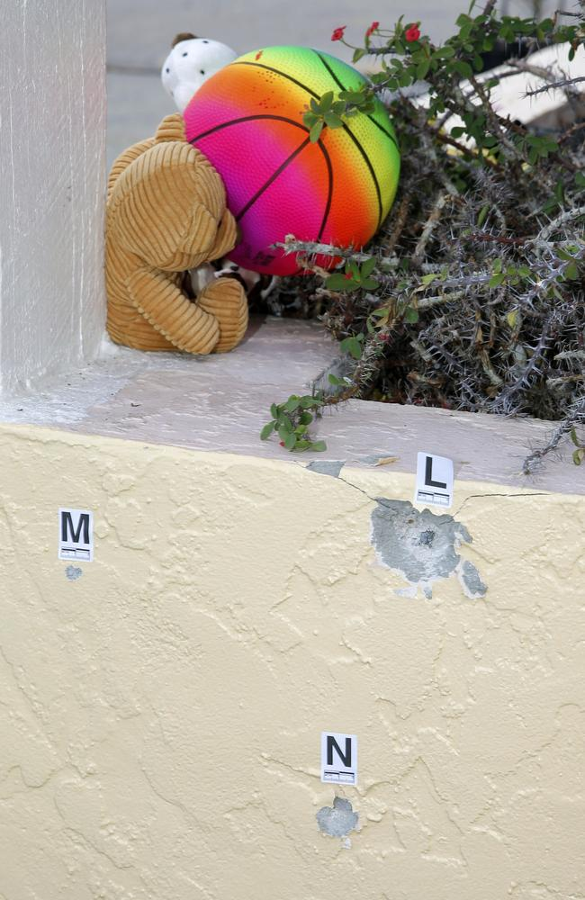 Mourners leave teddy bears at a memorial near a wall covered in bullets at Club Blu in Fort Myers, Florida. Picture: Mike Carlson/Getty Images/AFP