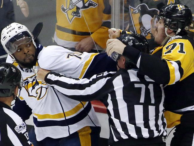 Nashville Predators' P.K. Subban, left, and Pittsburgh Penguins' Evgeni Malkin, right, square off as linesman Brad Kovachik tries to separate them.