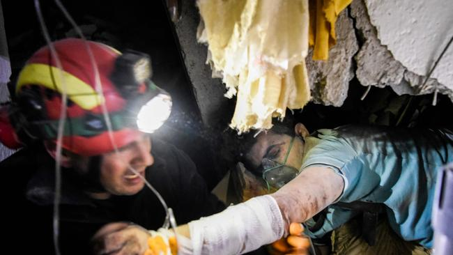 A firefighter tries to rescue a man stucked in the ruins of a collapsed building.