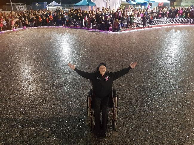 Connie Johnson in a heart of 5 cent pieces at the end of the Big Heart Project. Picture: Love Your Sister/Facebook