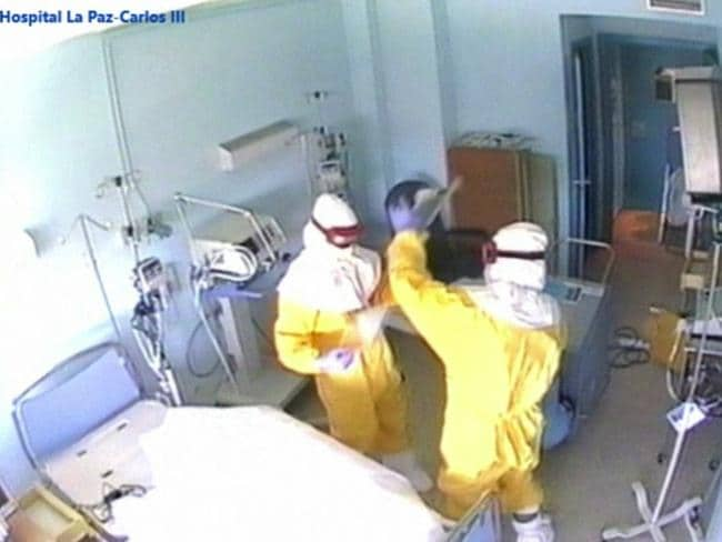 Medical workers clean the Madrid hospital room of priest Miguel Pajares, who died in August after contracting Ebola, in a video released by the local health authority.