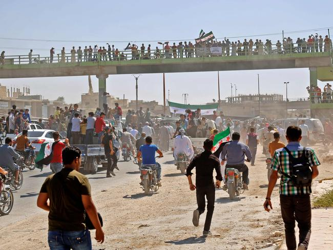 Syrians chant slogans and wave flags of the opposition as they protest against the regime and its ally Russia, in the rebel-held town of Maarrat al-Numan in the north of Idlib province. Picture: AFP
