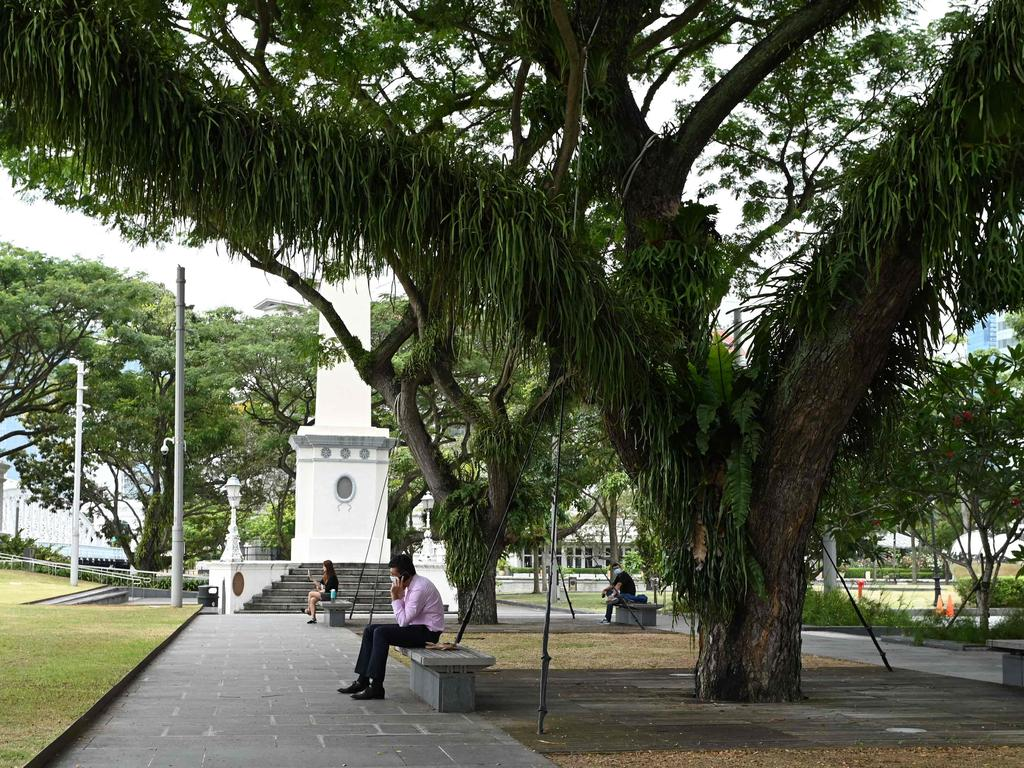 People relax at the park next to Raffles Place financial business district in Singapore on Tuesday. Picture: Roslan Rahman