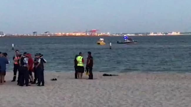 Emergency services and locals at the Brighton Le Sands Beach after the man's body was pulled to shore.