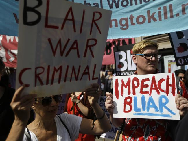 Protesters hold placards outside the Queen Elizabeth II Conference Centre in London, shortly before the publication of the Chilcot report. Picture: AP