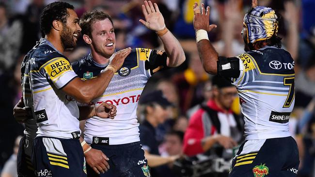 Michael Morgan celebrates with Justin O'Neil and Johnathan Thurston of the Cowboys.