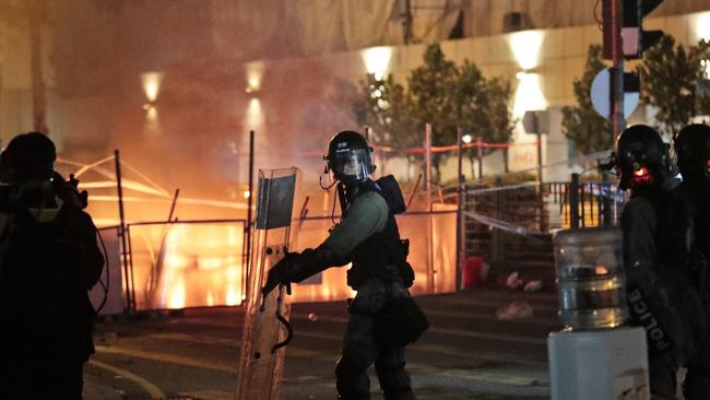 Police officers take their position as barricades lit by protesters burn. Picture: AP