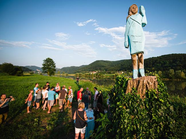 People gather around what conceptual artist Ales 'Maxi' Zupevc claims is the first ever monument of Melania Trump, set in the fields near the town of Sevnica. Picture: Jure Makovec/AFP.