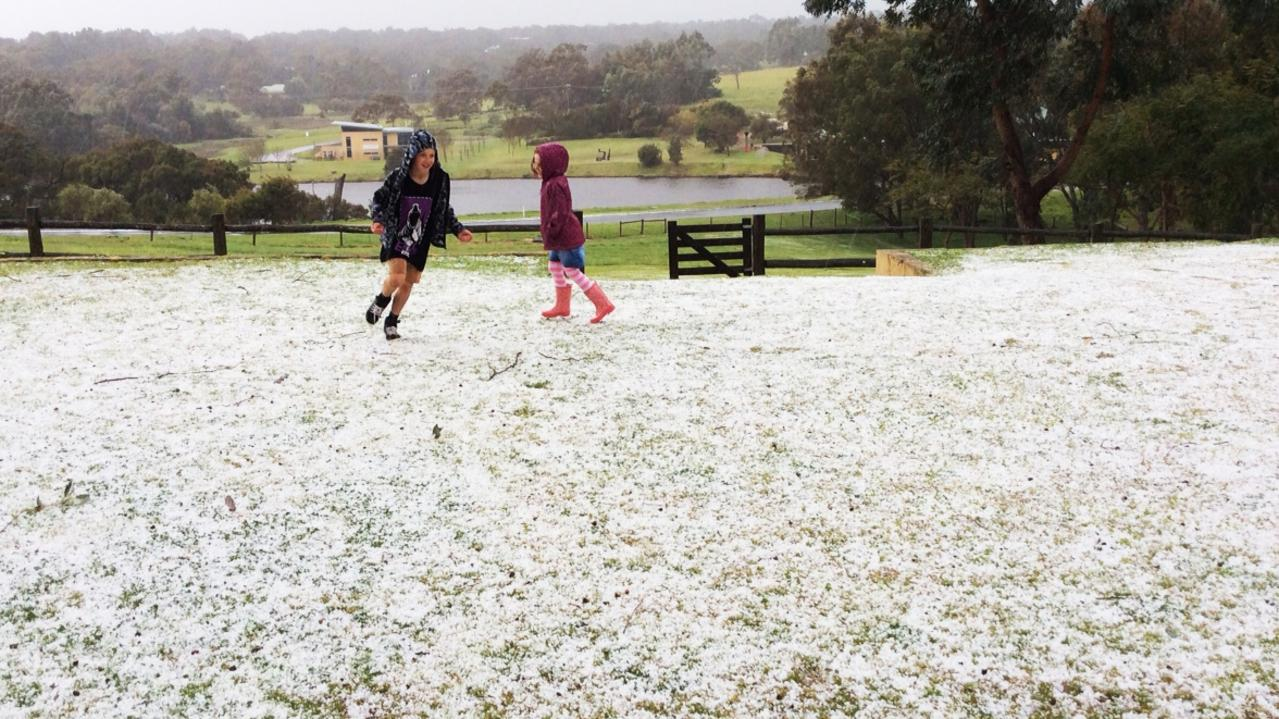 Charlie Watts and Billie Taylor play after a hailstorm hit Gunyulgup Valley, near Yallingup. Picture: Rod Taylor