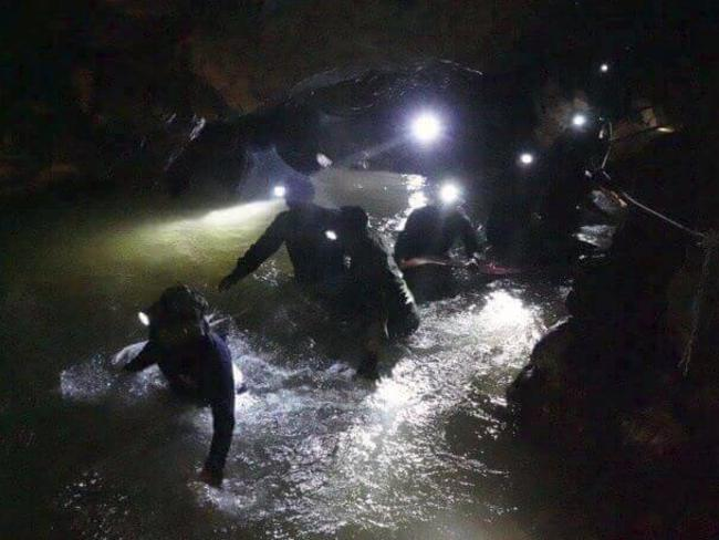 Thai rescue teams walk inside the cave complex where 12 boys and their soccer coach are trapped. Picture: AP