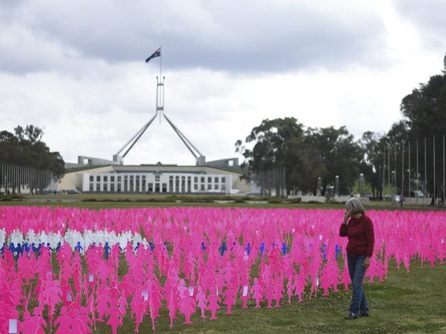 A woman looks at 6000 pink silhouettes staked into the ground for a breast cancer memorial outside Parliament House in Canberra, Wednesday, October 17, 2018. Picture: AAP Image/Lukas Coch