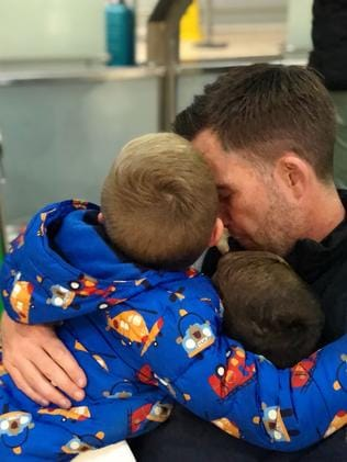 Group hug: the boys embrace their dad.