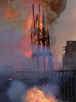 The steeple engulfed in flames collapses as the roof of the Notre-Dame de Paris Cathedral burns on April 15, 2019 in Paris. - A colossal fire swept through the famed Notre-Dame Cathedral in central Paris on April 15, 2019, causing a spire to collapse and raising fears over the future of the nearly millenium old building and its precious artworks. The fire, which began in the early evening, sent flames and huge clouds of grey smoke billowing into the Paris sky as stunned Parisians and tourists watched on in sheer horror. (Photo by Geoffroy VAN DER HASSELT / AFP)