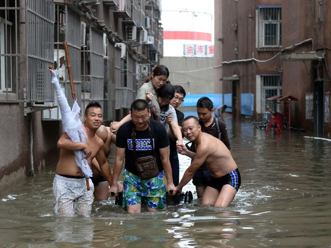 People attempt their way through a flooded area in Changping District in Beijing.