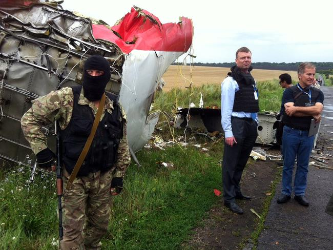 Danger zone ... Alexander Hug (second left), Deputy Chief Monitor of the Organisation for Cooperation and Security in Europe's (OSCE) Special Monitoring Mission to Ukraine, visits the site of the crash in rebel-held east Ukraine.