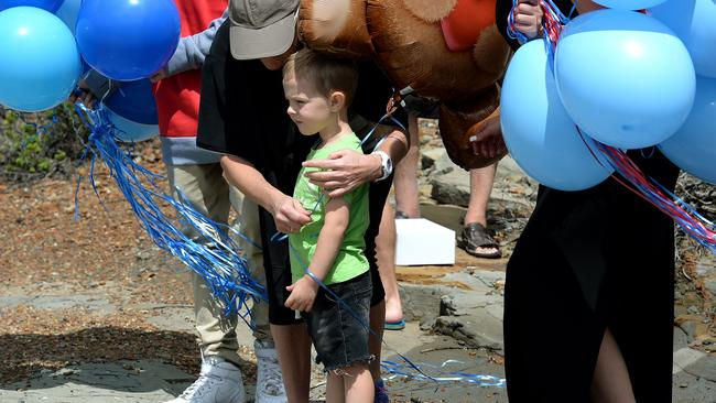 Jesse Howes' two-year-old son Chaise comforted by Jesse's brother Sam and his mum Kayla Walker as they pay tribute where he died off Snapper Point. Picture: Peter Lorimer..