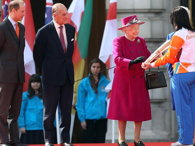 Australian cyclist Anna Meares with the Commonwealth Games baton, as the Queen, Prince Edward and Prince Phillip look on. Picture: Tim P. Whitby/Getty Images