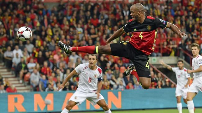 Belgium's Vincent Kompany jumps to kick the ball