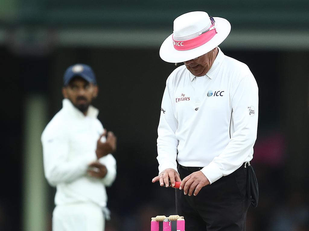 Umpire Ian Gould takes a light reading.