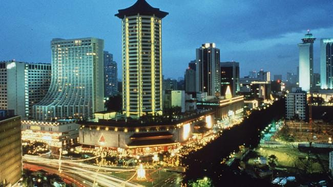 Orchard Road shopping district by night and the city skyline of Singapore.