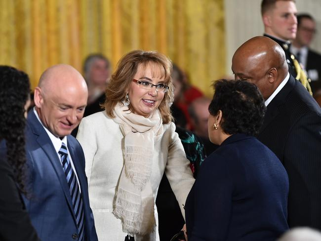 Support ... former congresswoman and gun violence victim Gabrielle Giffords (centre) and her husband astronaut Mark Kelly (left) at the White House to hear Barack Obama's address. Picture: AFP/Mandel Ngan