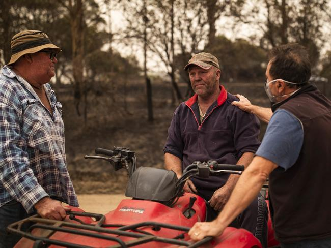 Beef farmer Steve Shipton (centre) is consoled by fellow farmers Bernie Smith (left) and Peter Mercieca in Coolagolite, NSW on New Year's Day. Picture: Sean Davey/AAP