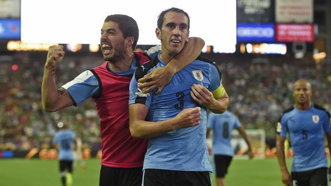 Uruguay's Diego Godin (R) celebrates with teammate Luis Suarez.