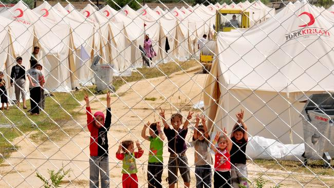 Syrian refugee children wave from the Boynuyogun Turkish Red Crescent camp in the Altinozu district of Hatay, Turkey near the Syrian border. Picture: AFP MUSTAFA OZER