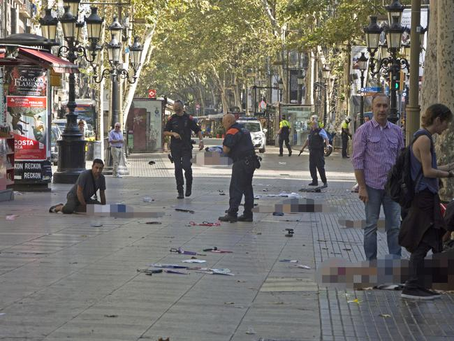 Police officers attend injured people moments after a van crashes into pedestrians in Las Ramblas, downtown Barcelona. Picture: EFE News Agency