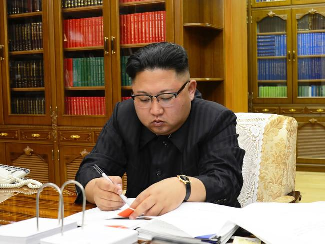North Korean leader Kim Jong-un signs the order to carry out the test-fire of the intercontinental ballistic missile Hwasong-14. Picture: KNCA/AFP